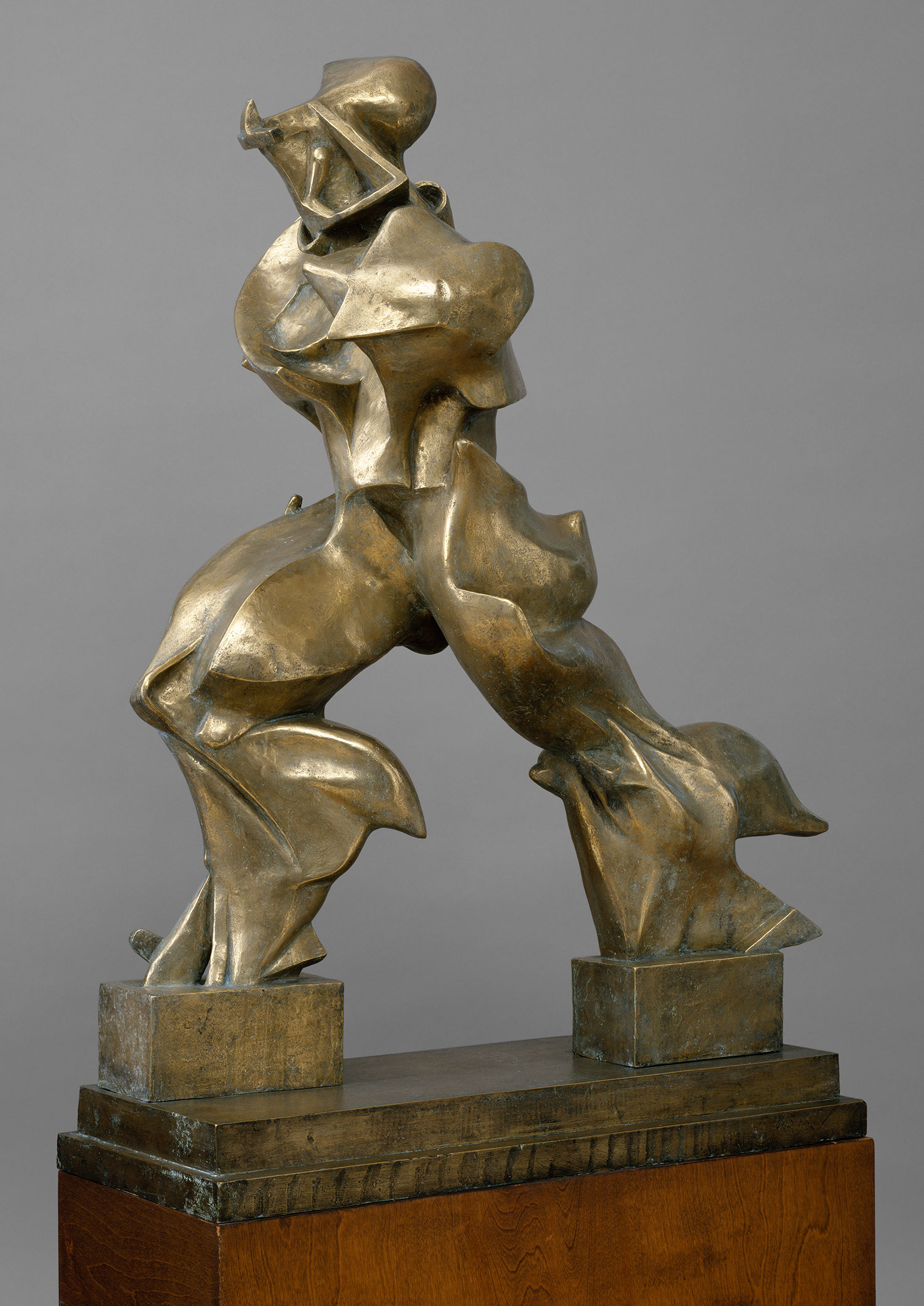 Unique Forms of Continuity in Space depicts a human-like figure seemingly flying or gliding through air. A clinging drapery whips back around his legs, giving the sculpture an aerodynamic and fluid form. Instead of a traditional pedestal, the figure is only bound to the ground by two blocks at his feet. The figure is also armless and without a discernibly real face.