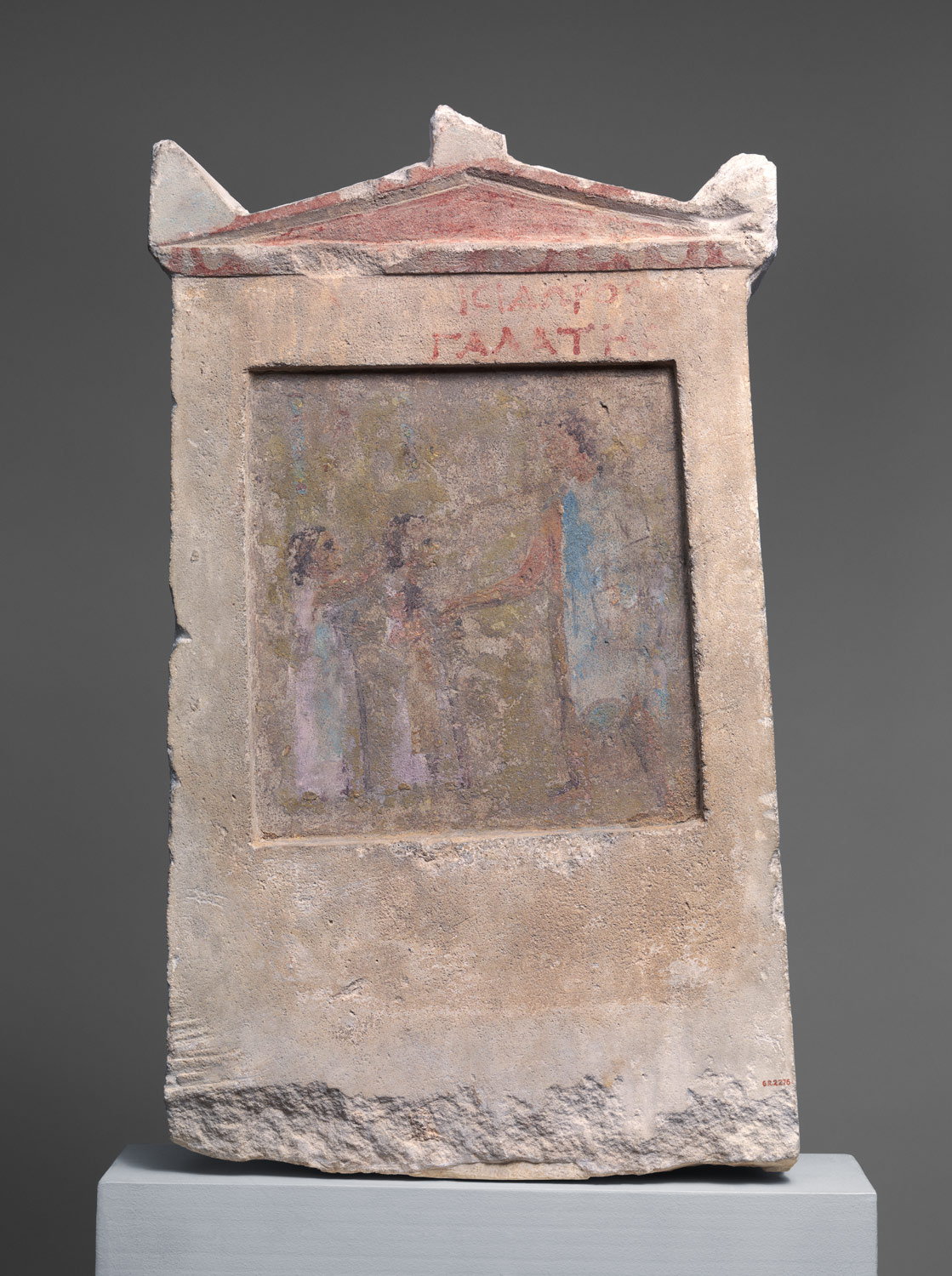 Painted limestone funerary slab with a soldier and two girls