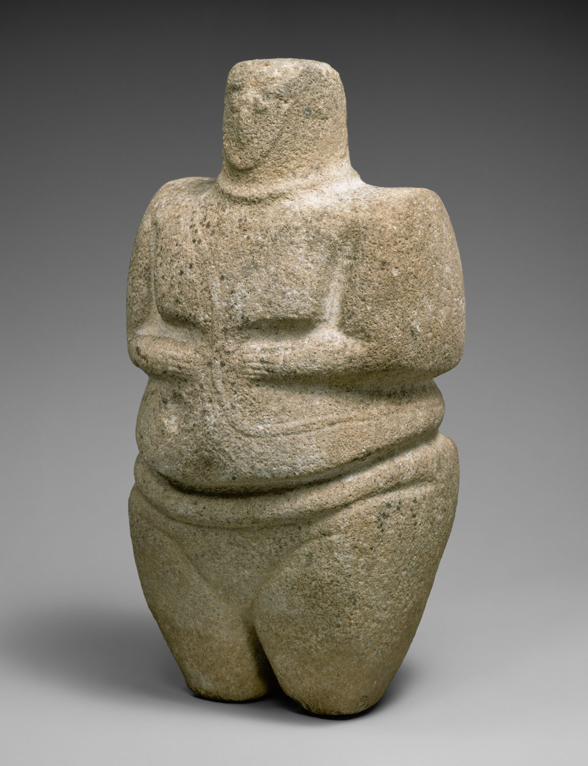 Standing female figure wearing a strap and a necklace