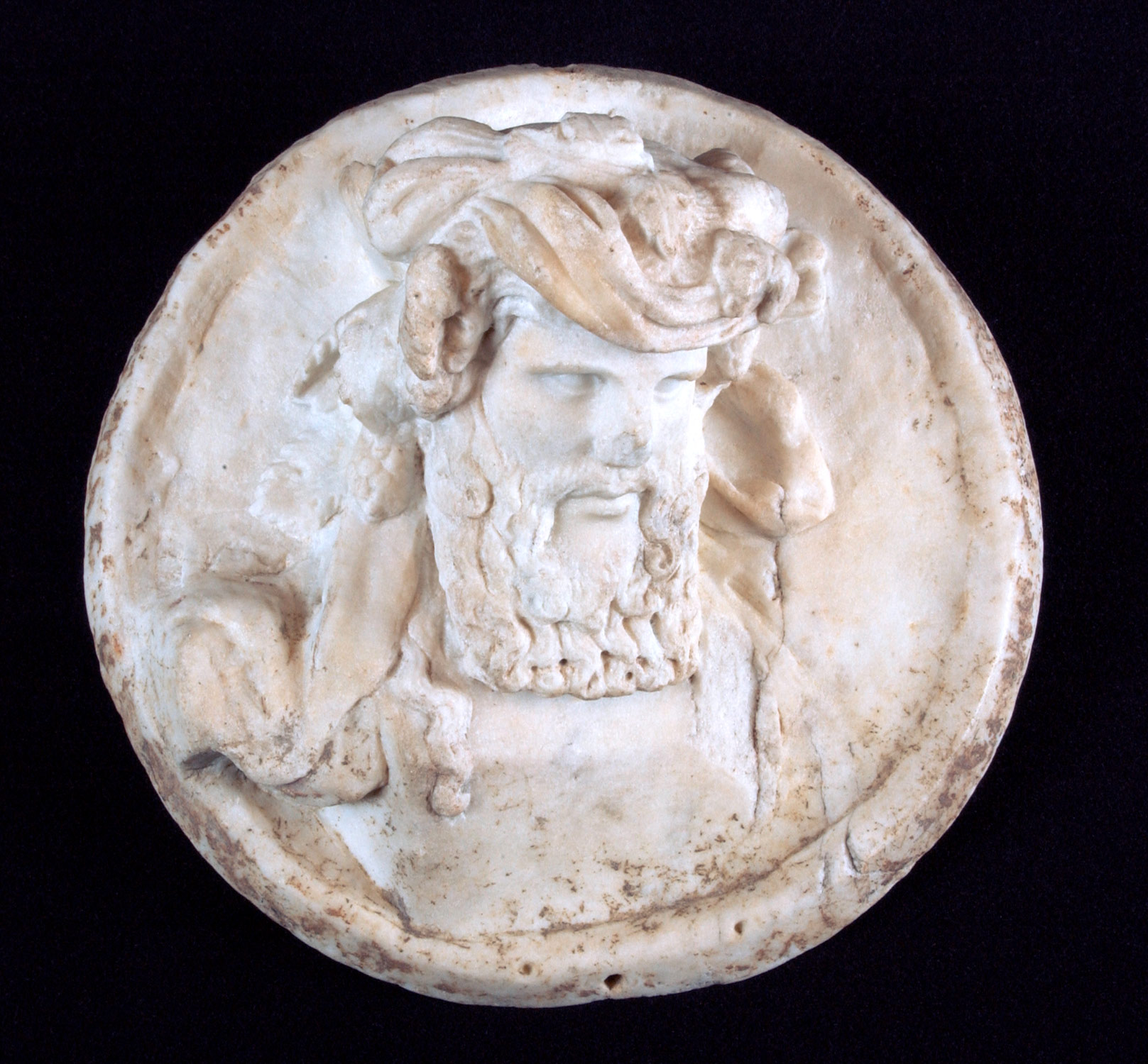 Marble disk with a herm of Dionysus in relief