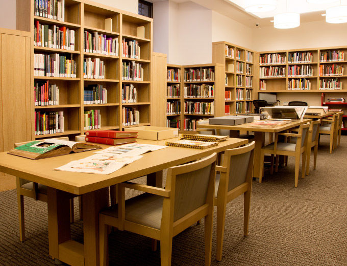 A bright, modern, blonde wood library lined with shelves of books and tables with comfortable chairs