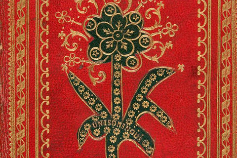 A bright red leather book binding decorated with engraved floral motifs painted dark green, and gilt borders