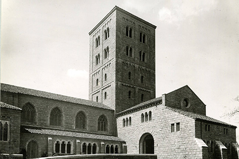 A black-and-white photograph of a low stone building with two wings faced by arches and a large central, four-story tower with tall, narrow arched windows