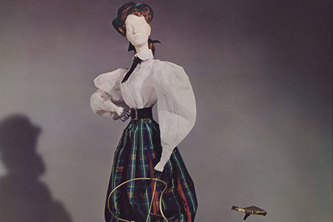 A female miniature doll dressed in a white mutton-sleeved blouse, and a plaid skirt with a very narrow waist; beside her is a mid-nineteenth-century bicycle