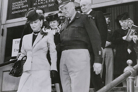 A black-and-white photograph of an older man in military costume and a woman dressed in a day suit, descending a staircase