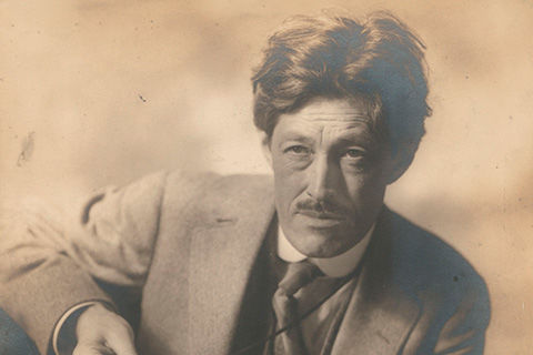A sepia-toned photograph of a man with floppy, disheveled hair and trim mustache dressed in an early-twentieth century suit and tie; he appears to be caught in the middle of doing something and is looking up at someone or something out of the frame