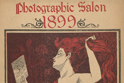 The cover of a catalogue, in red and black ink on white paper, depicting a woman grasping her long red hair high in her left hand and holding a book in her right hand; the catalogue is titled: Photographic Salon 1899