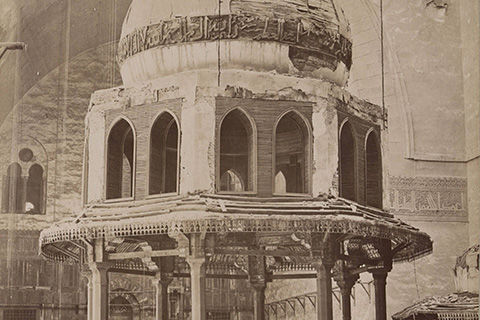 A sepia-toned photograph of the interior of a mosque, including a structure with an onion-shaped dome decorated with carved Arabic script along the outside