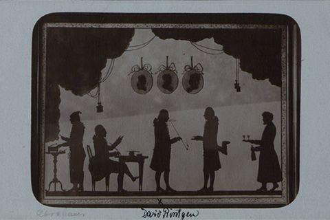 A portrait of silhouette paper cut-outs of figures in a nineteenth-century room: Four standing male figures, one seated male figure, and three busts in profile in pendants hanging on the wall