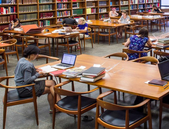 A large, modern, sunny room in a library lined with shelves of books; in the center are long rectangular wooden tables with chairs, students with laptops and books are working at the tables