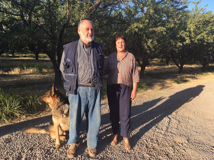 Two farmers and their German shepherd on an orchard in Chile