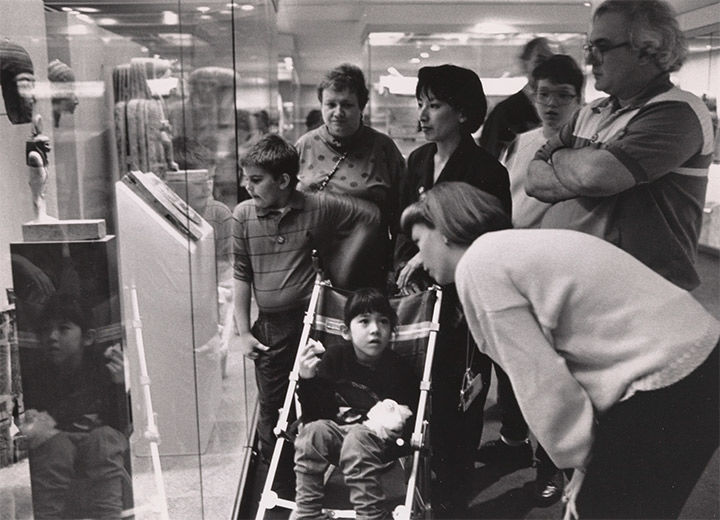 Archival photo of adults and children looking at Egyptian art.