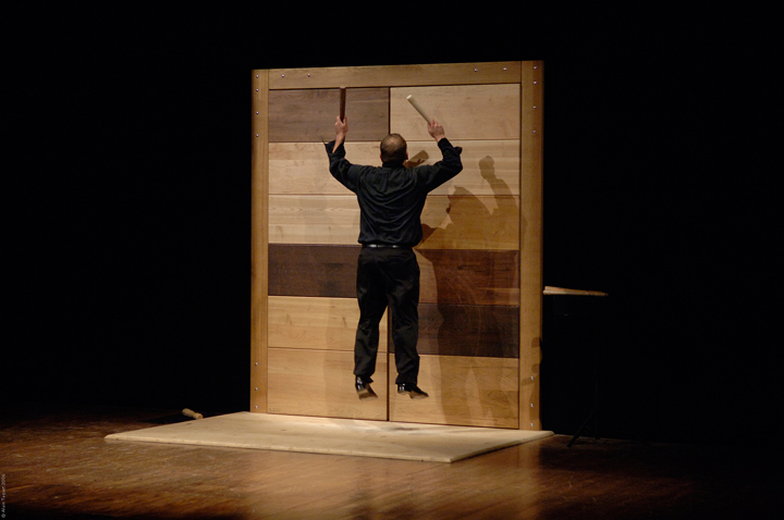 A percussionist jumps into the air to strike a large metal door with two hammers
