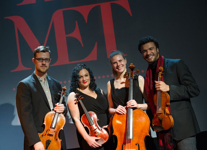 PUBLIQuartet pose in front of The Met's logo holding their instruments
