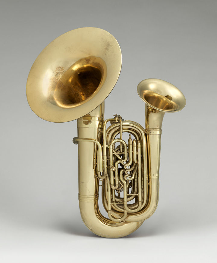 A brass instrument with two bells against a grey background