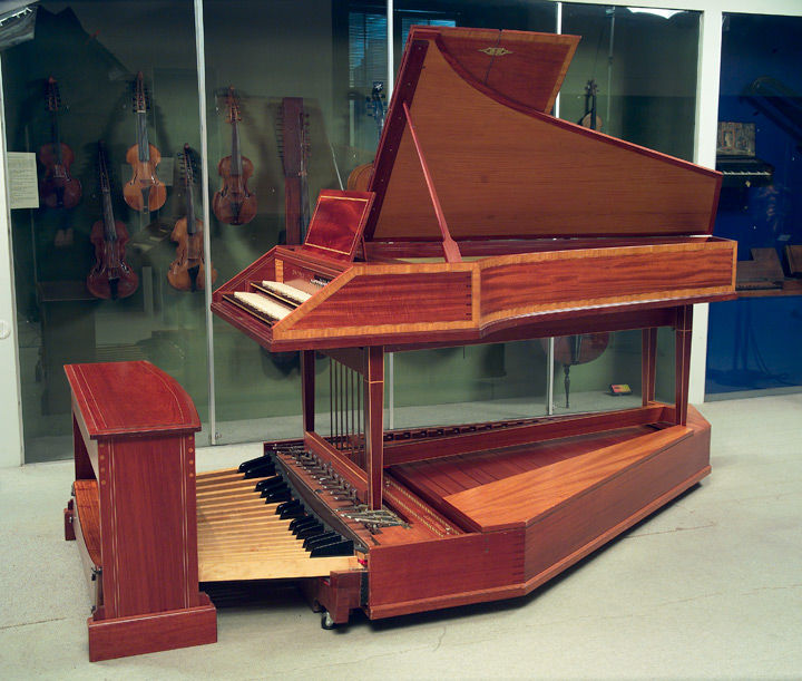 View of a pedal harpsichord in a gallery surrounded by an assortment of stringed instruments
