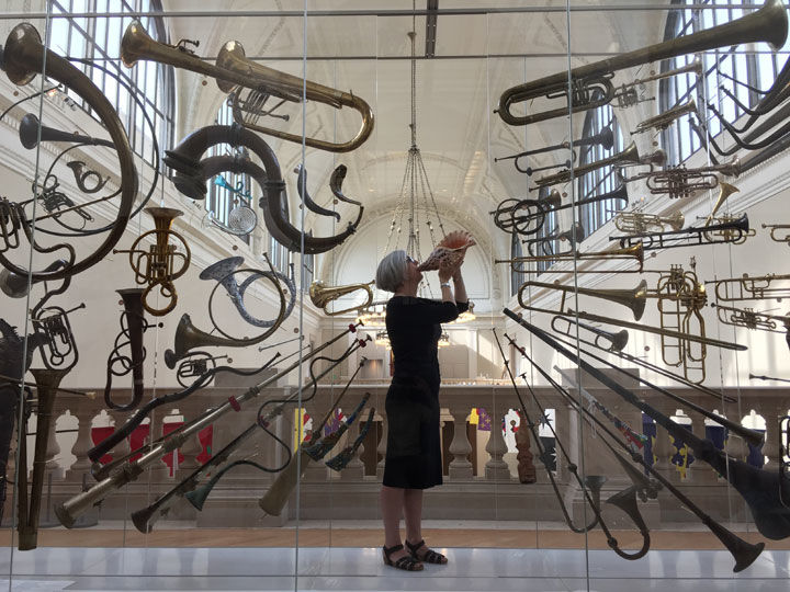 The author stands among a large display of brass instruments while blowing into a conch shell