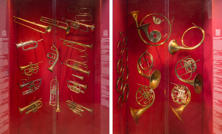 Views of two wall cases showing various trumpets and French horns