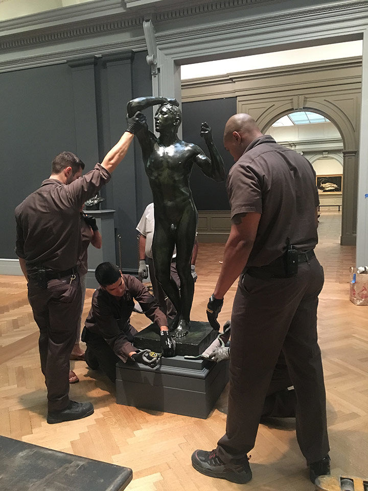 Museum rigger Luis Nuñez takes measurements to center The Age of Bronze on its base. Michael Doscher and Derrick Williams stand to his left and right.