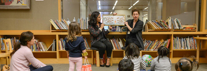 Two librarians read a book aloud to a group of children in a Museum library