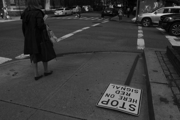 "Woman crossing the street next to a fallen sign reading ""Stop Here on Red Signal"""