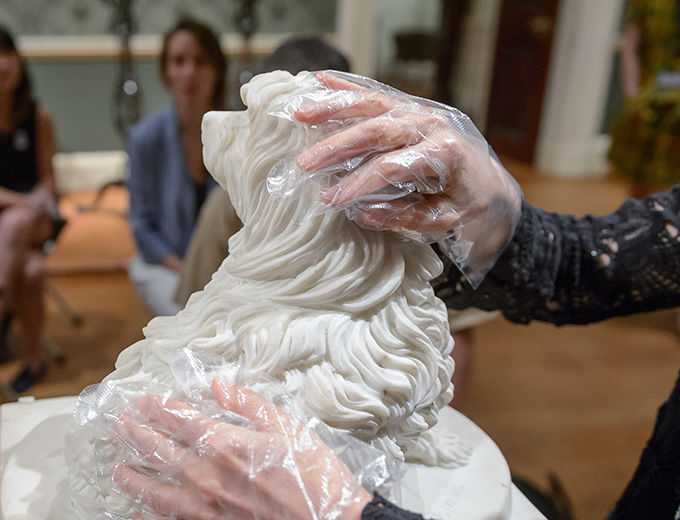 A visitor who is blind feels a sculpture through protective gloves