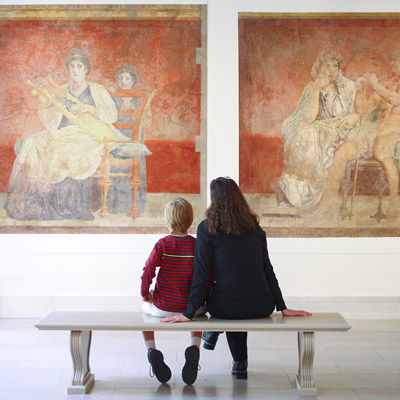 A woman and young child sitting on a bench in the Roman fresco gallery looking at art