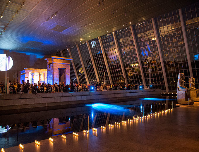 Large glass-enclosed gallery at night decorated with lit with candles and dramatic lighting for a party; in the center of the gallery is an ancient Egyptian sandstone temple