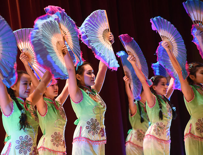 Young women in colorful Asian-inspired costumes dancing with large, colorful folding fans