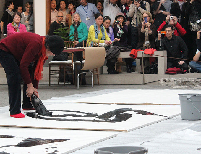 Woman bending over, painting with a very large brush dipped in black ink, on large white paper set on the floor