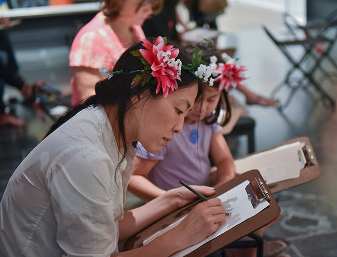 Mother and her daughter wearing flower crowns drawing in the galleries