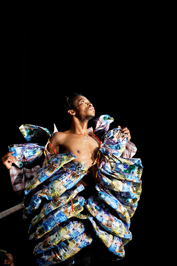 A male dancer wrapped in an elaborate costume made of different types of currency