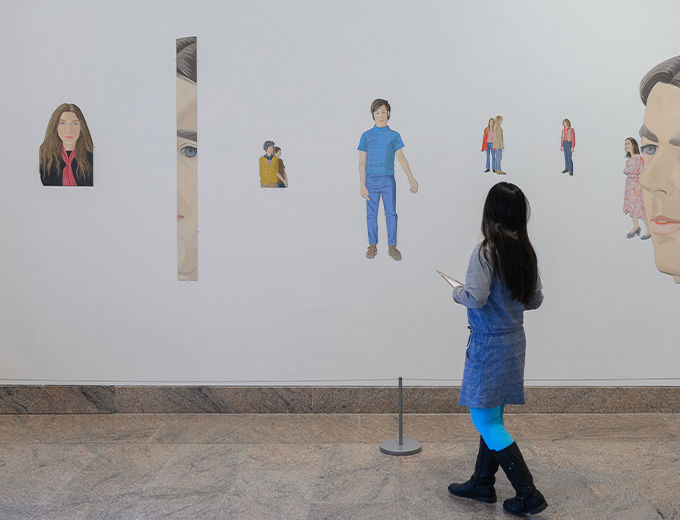 Young girl looking at a wall mural of very realistic portraits of people