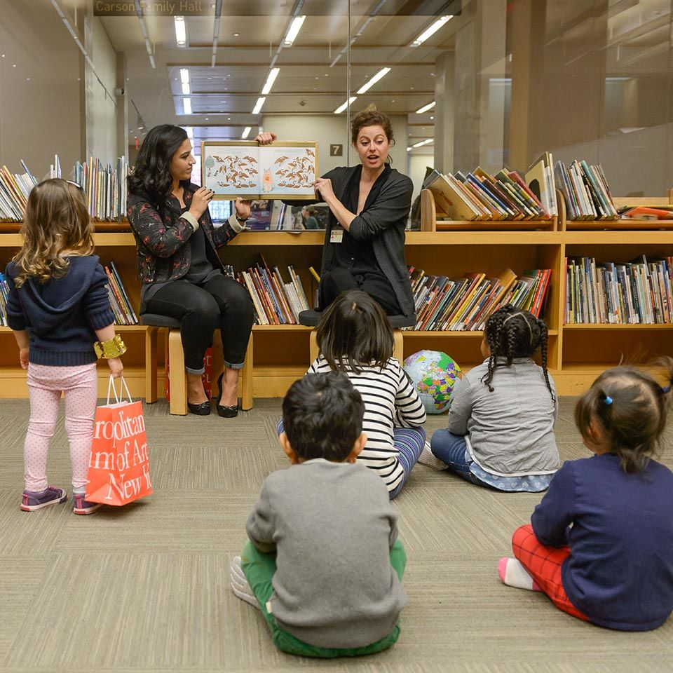 Young children sitting in a library listening to a story