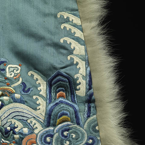 Detail of a blue silk garment with a fur edge