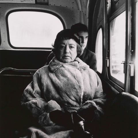Black-and-white photograph of a woman on a bus