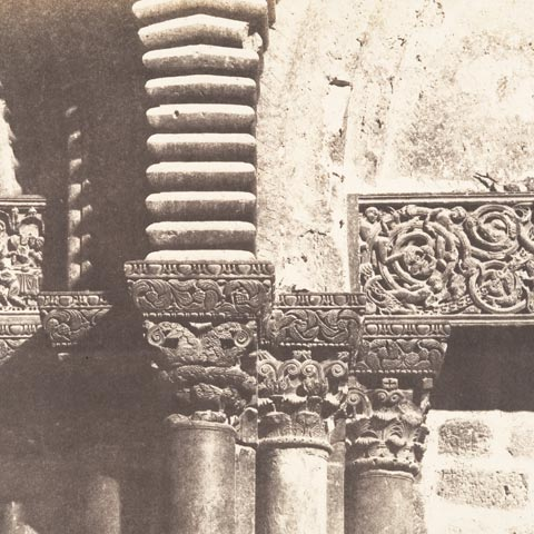 Faded photograph showing carved capitals atop stone columns