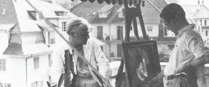 Black-and-white photo of the artist Paul Klee sitting on a balcony while his son, Felix Klee, looks at a painting