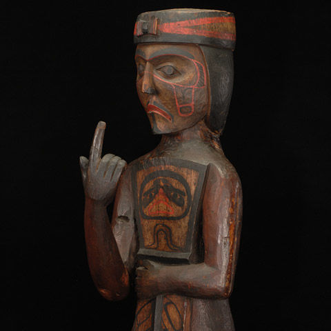 Wooden potlatch figure with index finger pointing up and left hand folded over belly
