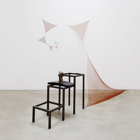 Installation view of a tiered steel structure with a series of triangular sheets of copper wire in the background
