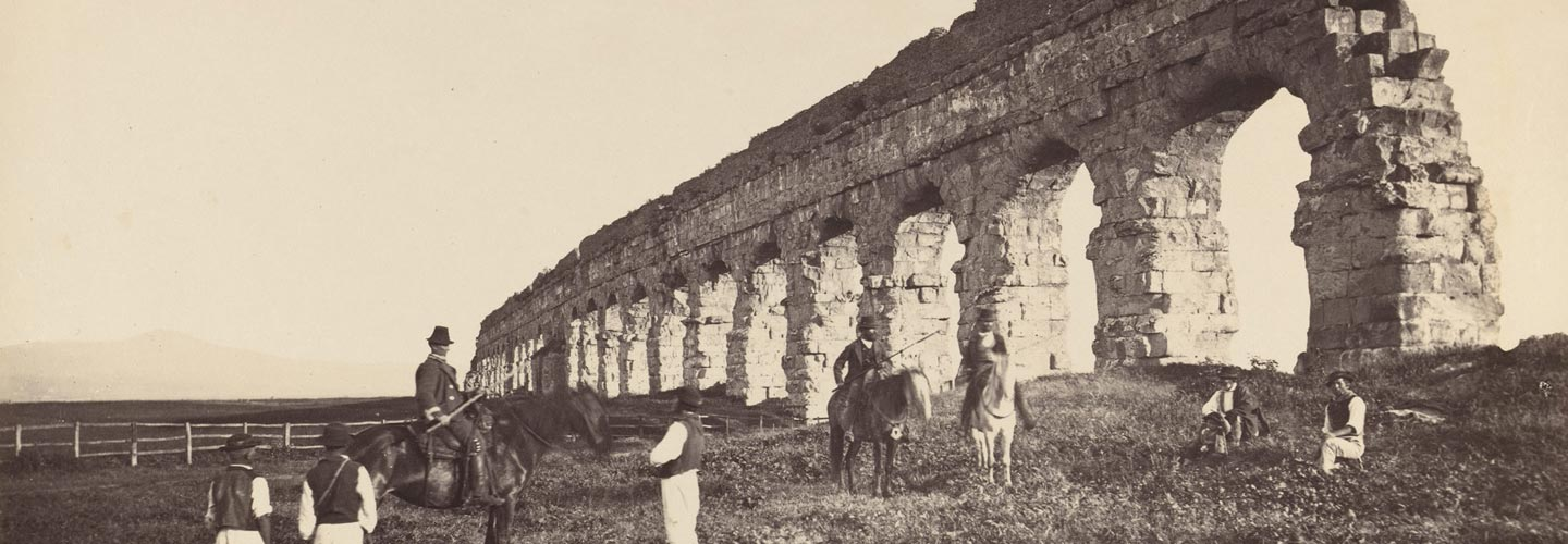 Mid-19th-century photograph of men on horseback near a Roman aqueduct