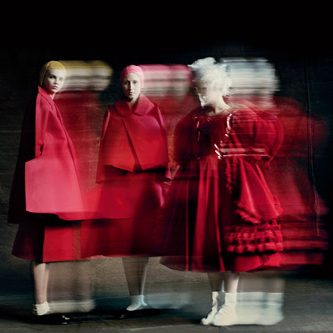 Two figures in red gowns against a black background