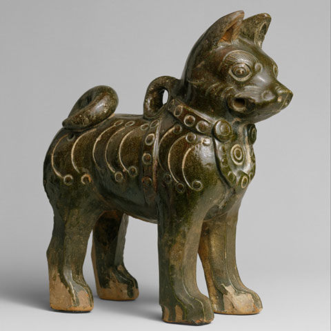 Earthenware figure of a dog with pointed ears and curved tail
