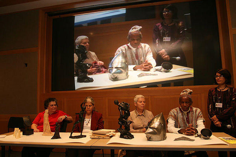 Five people at a table with sculptures and art objects on it; behind them is a large screen with a projection of the live procedings