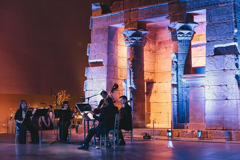 View of Temple of Dendur spectacularly lit for celebration with musicians