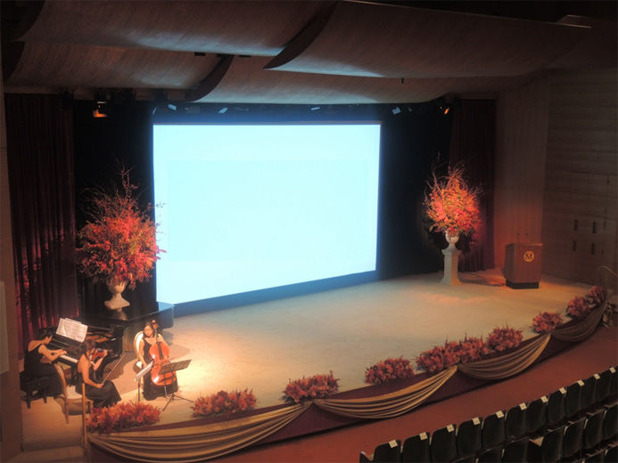 An elevated view of a large modern blonde wood auditorium as viewed from the balcony; on stage, the screen is lowered to show a projection and on either side of the screen are large vases filled with branches of autumn leaves red berries; stage right is a female classical musical group playing the piano, violin and cello