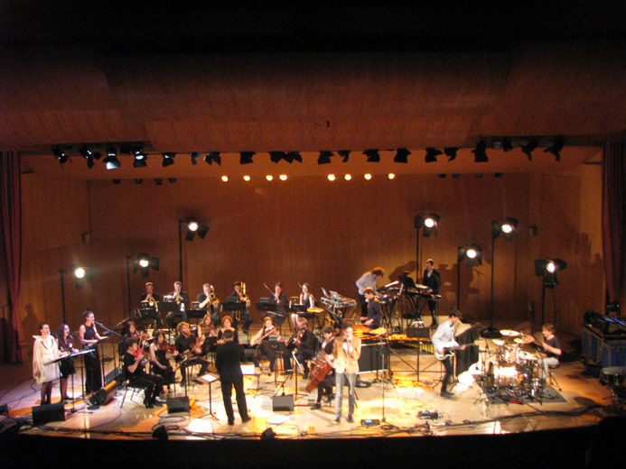 An elevated close-up of the stage of a large modern blonde wood auditorium as viewed from the balcony; on stage, is a large, modern orchestra