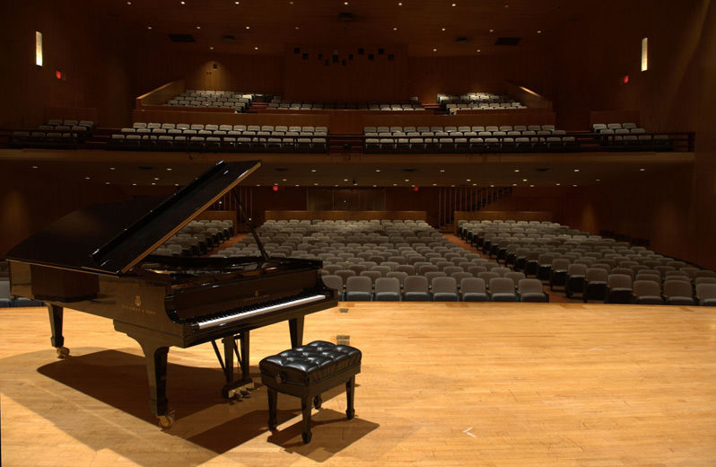 A large modern auditorium with two-tiered balcony as viewed from the stage; on the left side of the stage is a black grand piano with the lid and fallborad raised, and a padded piano bench in front