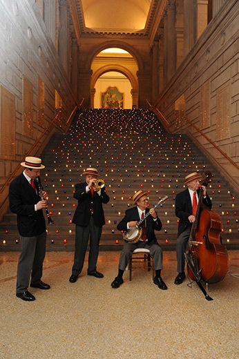 Four musicians playing in front of the grand staircase