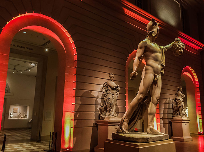 View of heroic nude sculpture in Petrie Court, spectacularly lit